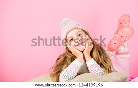 Kid girl wear cute knitted fashionable hat and scarf accessory. Winter accessory concept. Girl long hair dream pink background. Kid dreamy face wear knitted accessory. Winter fashion accessory.