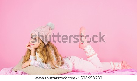 Kid girl wear cute knitted fashionable hat and scarf accessory. Winter fashion accessory. Winter accessory concept. Girl long hair dreamy mood pink background. Kid smiling wear knitted accessory.