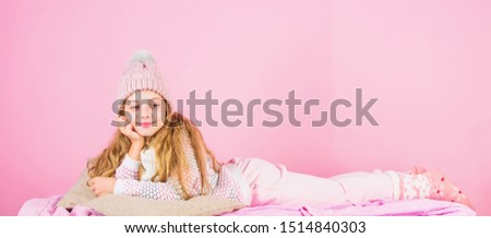 Kid girl wear cute knitted fashionable hat and scarf accessory. Winter fashion accessory. Winter accessory concept. Girl long hair dream pink background. Kid dreamy face wear knitted accessory.
