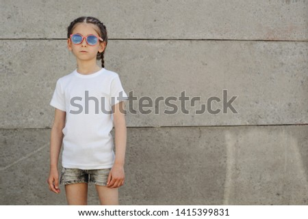 Kid girl wearing white t-shirt with space for your logo or design in casual urban style #1415399831