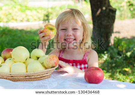 Kid girl with apples in the garden - stock photo
