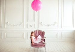 Kid girl 4-5 year old sitting in armchair holding pink balloon in room over white background. Looking at camera. Childhood. Cute little princess.