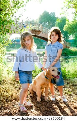 kid girls with Golden retriever puppy outdoor park river