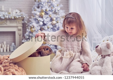 kid got a pet for Christmas. the bedroom is decorated with a Christmas tree. happy child opens the gift box. delight and surprise at the surprise. in the new year dreams come true. applied calibration #1237944055