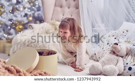 kid got a pet for Christmas. the children's room is decorated with a Christmas tree. happy child opens the gift box. delight and surprise at the surprise. in the new year dreams come true. calibration #1237943992