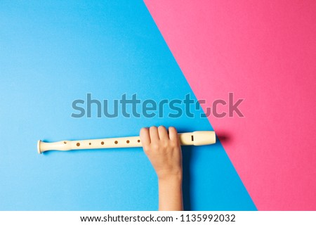 Kid hand with flute on colorful background #1135992032