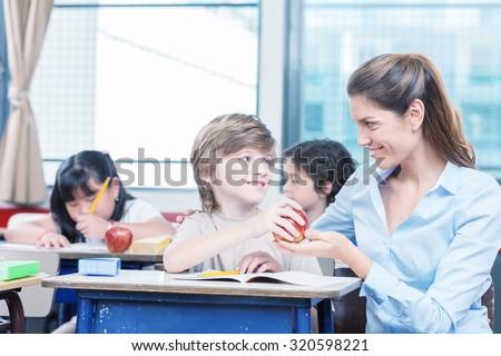 Kid handing red apple to teacher in elementary school.