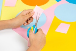 Kid hands cutting colored paper with scissors. Education, learning, paper craft, entertainment at home