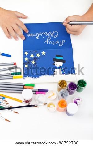 Kid hands making christmas postcard