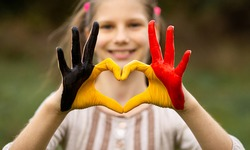 Kid hands painted in Belgium flag color show symbol of heart and love gesture on nature background. Focus on hands