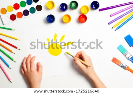 Kid hands painting yellow sun. Top view to white table with art supplies Сток-фото ©