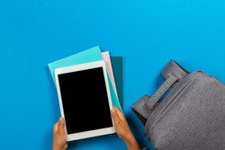 Kid hands with tablet computer, notebooks, books and gray backpack over light sky blue background