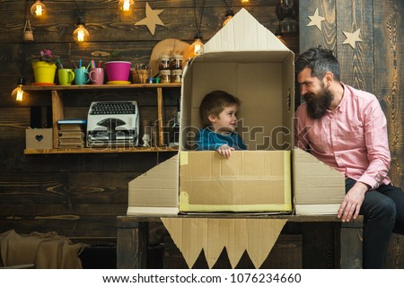 Kid happy sit in cardboard hand made rocket. Boy play with dad, father, little cosmonaut sit in rocket made out of cardboard box. Rocket launch concept. Child cute boy play cosmonaut, astronaut.