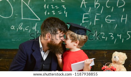 Kid happy studies individually with father, at home. Individual schooling concept. Father with beard, teacher teaches son, little boy. Teacher and pupil in mortarboard, chalkboard on background. #1187938855