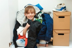 Kid hiding among messy clothes inside closet. Organization and storage of clothes at home. Mess in the wardrobe. Boy with messy colorful clothing at room. Untidy clutter clothing closet.