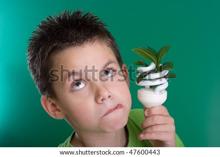 Kid holding a compact fluorescent bulb with a leaf. Global warming concept. On green backdrop