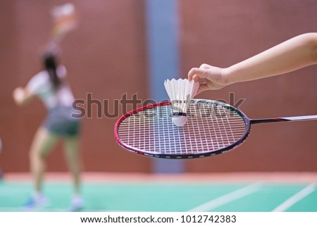 kid holding badminton racket and shuttlecock in badminton court.