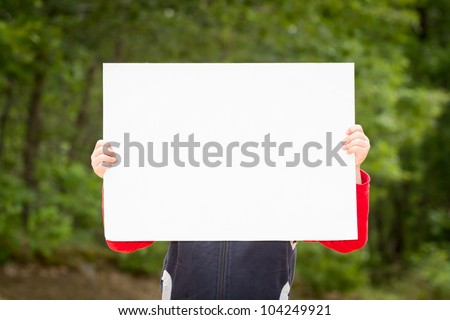 Kid holding empty paper in hands