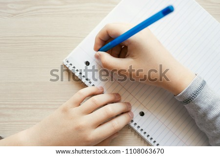 Kid holding pen and writing in notebook. Close up, top view.