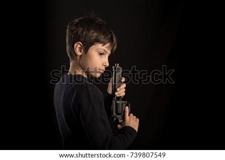 Kid holding toy gun. Studio portrait against black background.