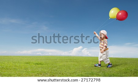 kid holding two balloon and enjoying himself