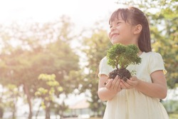 Kid holding young plant in hands against spring green background. Ecology concept