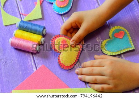 Kid holds a felt heart in his hand. Kid made a felt heart. Colorful felt hearts, scissors, thread on a wooden table. St. Valentines Day crafts concept. Simple hand sewing projects idea for children