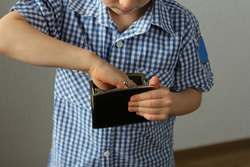 kid holds a wallet and takes out with his hand, the concept of pocket money, theft, shopping