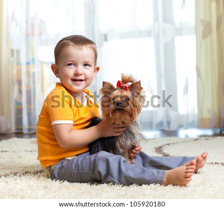 kid hugging puppy indoor - stock photo