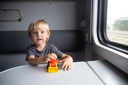 Kid in a train compartment looks out the window. The passenger with a toy travels in the train cabin.