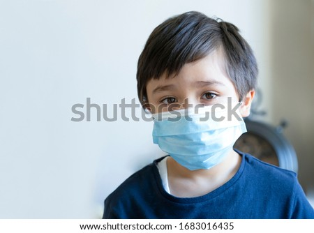 Kid in isolation wearing medical protection face mask with sad face,Child boy feeling bored have to stay at home during corona virus home quarantine, Protective measures against spreading of Covid-19