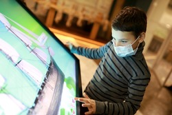 Kid in mask using touch screen in museum