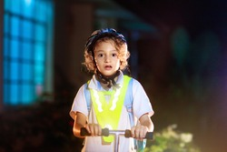 Kid in reflective vest in darkness. Safety on dark city streets for school children. Safe way home at night or in the evening. Fluorescent stripes on kids clothing and backpack. Boy walking at dusk.