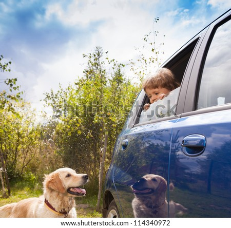 kid in the car and dog outside look at each other - stock photo