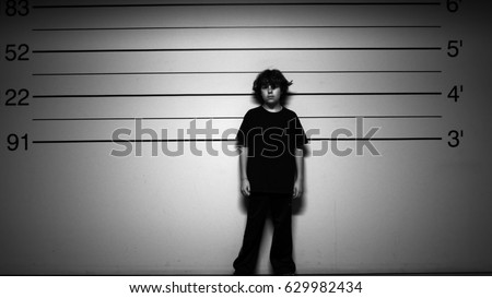 KID IN TROUBLE.  BLACK AND WHITE SHOT OF A YOUNG BOY IN A POLICE LINE UP.  MODEL RELEASE. - Shutterstock ID 629982434