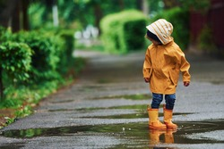 Kid in yellow waterproof cloak and boots playing outdoors after the rain.