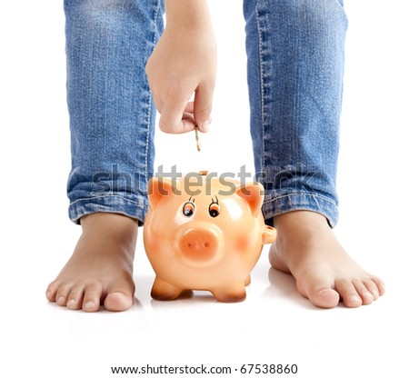 Kid inserting one euro coin on the piggy-bank