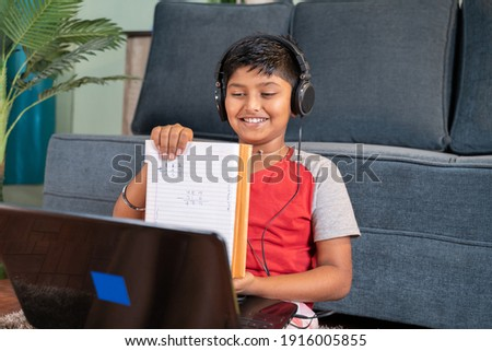 Kid interacting during online class by showing solved problems to tutor on laptop - concept of new normal virtual education and e-learning due to covid-19 pandemic