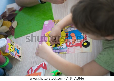Kid is gluing a sticker on applique. #748471846