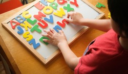 kid is Learning the alphabets at home.