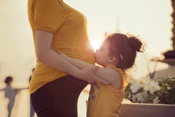 kid kissing the belly of her mom