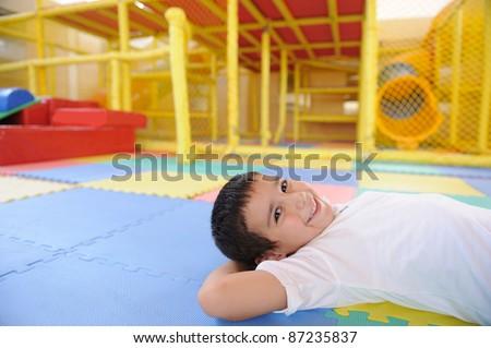 Kid laying on ground in the kindergarten