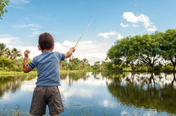 Kid learning how to fish, holding a rod on a lake