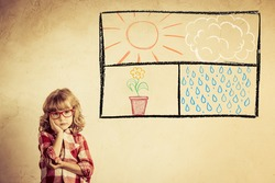 Kid looking out of the drawn open window on grunge wall. Freedom concept