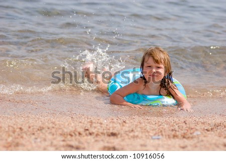 Kid lying on the beach in warm sea transparent water looking at you with smile