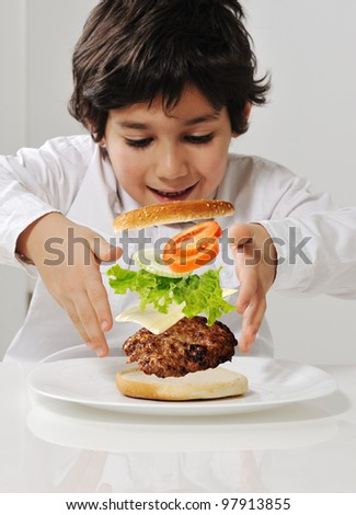 Kid making burger by himself - stock photo
