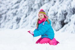 Kid making snowman in snowy winter park. Children play in snow. Little girl in colorful jacket and hat building snow man in winter garden after snowfall. Outdoor fun on cold winter day.