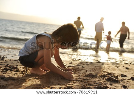 Kid on beach in sand playing, people around, summer hot nice time