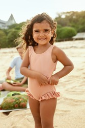 Kid On Beach Portrait. Tanned Little Girl In Swimsuit Standing On Sandy Coast And Looking At Camera. Summer Vacation With Children At Tropical Resort As Lifestyle.