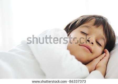 Stock Photo Kid on sleeping bed, happy bedtime in white bedroom